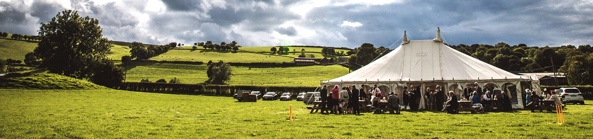 Traditional Wedding Marquee in field with beautiful backdrop
